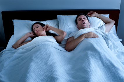 A man sleeping with his mouth open snoring loudly keeping his wife awake.