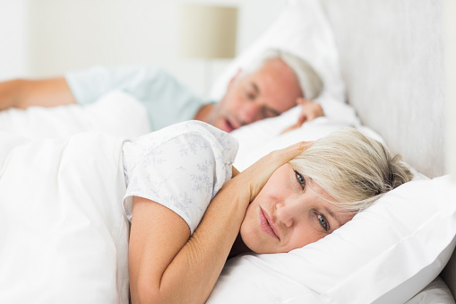 Couple in bed with husband snoring and wife covering her ears.